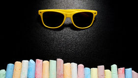 Colored chalks aligned on blackboard.  Royalty Free Stock Photos