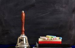 Colored chalks and a bell in front of a chalkboard Royalty Free Stock Image