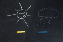 Colored chalks, black blackboard with drawings of sun and a cloud Stock Photo
