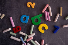 Colored chalks numbers and letters on blackboard Stock Photos