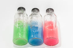 Colored chemicals, glass bottles on a white background Stock Photos