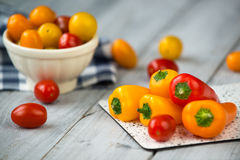 Colored cherry tomatoes and mini paprika on a wooden table Royalty Free Stock Photos