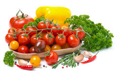 Colored cherry tomatoes in a wooden bowl, pepper, herbs Stock Photography