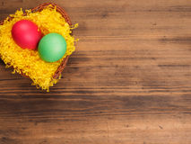 Colored chicken egg on background of bright yellow straw and old wooden table. The view from the top. Royalty Free Stock Photography