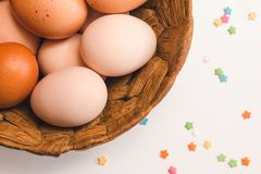Colored chicken eggs in a wicker brown basket and pastry decorations royalty free stock photography