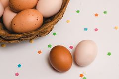 Colored chicken eggs in a wicker brown basket, two eggs and pastry decorations royalty free stock image