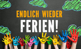 Colored children hands with the message `finally holidays`. In German Stock Photo