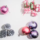 Colored Christmas balls, cones and gift boxes on a white background. Space for text, festive decor stock photos