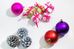 Colored Christmas balls, cones and gift boxes on a white background. Space for text, festive decor royalty free stock photos
