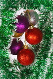 Colored Christmas balls on a green tinsel Stock Photography