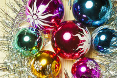 Colored Christmas balls and tinsel on a wooden background Royalty Free Stock Image