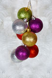 Colored Christmas balls on a white tinsel Royalty Free Stock Photo