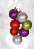 Colored Christmas balls on a white tinsel Stock Images
