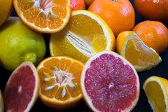 Colored Citrus fruits on a dark blue background. Slices of citrus and peel. Citrus reticulata. Citrus paradisi. Citrus limon. Citrus sinensis stock image