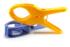 Colored clamps. Blue and yellow plastic clamps on white background Royalty Free Stock Images