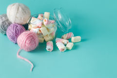 Colored clew of yarn for knitting and clored marshmallow Stock Photos