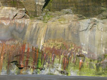Colored cliff- face. A seaside cliff- face with multi-colored patterns caused by the tide stock image