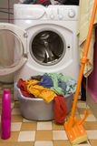 Colored clothes. Colored washed clothes in a basket and waching machine Stock Photo