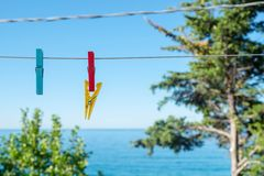Colored Clothespins hanging on a white cable with blue sea and sky background. Three colored Clothespins hanging from a cable in front of a blue sky and sea Royalty Free Stock Photos