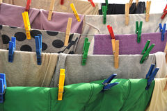 Colored clothespins hold the clothes on a rope. Close-up of colorful laundry pins and hanged clothes drying Stock Images