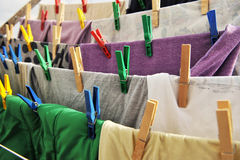 Colored clothespins hold the clothes on a rope. Close-up of colorful laundry pins and hanged clothes drying Stock Photos