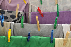 Colored clothespins hold the clothes on a rope Stock Photos