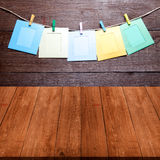 Colored clothespins with photo frames on rope on a wooden wall o Stock Photo
