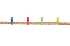 Colored clothespins on a rope. Isolated over whine background Royalty Free Stock Images