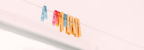 Colored clothespins on a rope on a blurred background. Some colorful clothespins are hanging on a washing line in front of green trees, long banner royalty free stock photography