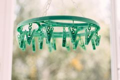 Colored clothespins on a rope on a blurred background. Some colorful clothespins are hanging on a washing line in front of green trees royalty free stock image