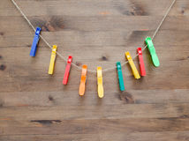 Colored clothespins and rope on  wood background Royalty Free Stock Photos