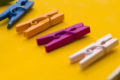 Colored clothespins on a yellow background royalty free stock photos