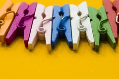 Colored clothespins on a yellow background stock image