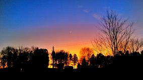 Colored clouds at twilight. A sliver of the moon hangs against silhouette of tress Royalty Free Stock Image