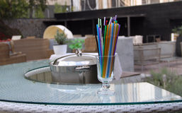 Colored cocktail straws in clear glass on the bar desk Stock Photo