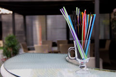 Colored cocktail straws in clear glass on the bar desk Stock Images