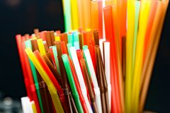 Colored plastic cocktail tubes standing in a glass top view, Drinking straws royalty free stock image