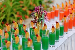 Colored cocktails. Buffet banquet table colorful drinks on a long white table Stock Images