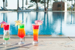 Colored cocktails on a background of water. Royalty Free Stock Photo