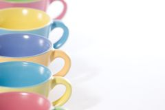 Colored coffee cups to the left Royalty Free Stock Photos
