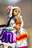 Colored colored puppet  on blurred background in Cusco. Hand made colored puppet in Cusco market. Women face with traditional Peruvian Quecha clothes and Stock Photos