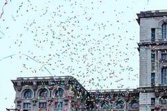 Colored confetti falling, blue sky in a european city, close up stock photos