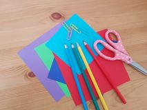 Arts and Crafts Supply, Kids Crafts, Back To School, School Supplies. Colored craft paper with colored pencils laying on a wooden background, Art teacher, Craft stock photo