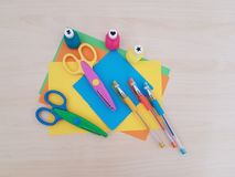Arts and Crafts Supply, Kids Crafts, Back To School, School Supplies. Colored craft paper with craft tools laying on a wooden background, Art teacher, Craft stock photo