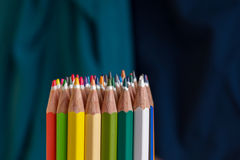 Colored crayon tips. Bunch of coloured crayons tips on a blue background stock photo
