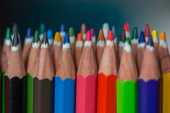 Colored crayon tips. Colored bunch of crayons on a white table with a bluebackground royalty free stock photo