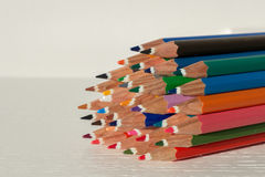 Colored crayon tips. Colored bunch of crayons on a white table with a white background royalty free stock photo