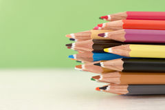 Colored crayon tips. On a green background Stock Images