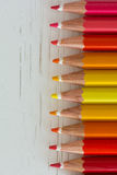 Colored crayon tips. On a wood pattern white background Stock Photos