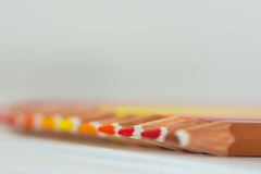 Colored crayon tips. On a wood pattern white background royalty free stock photos